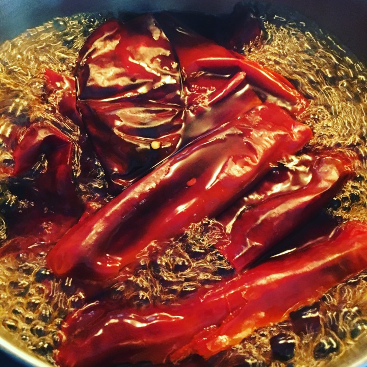 Red chiles boiling from a dried state.