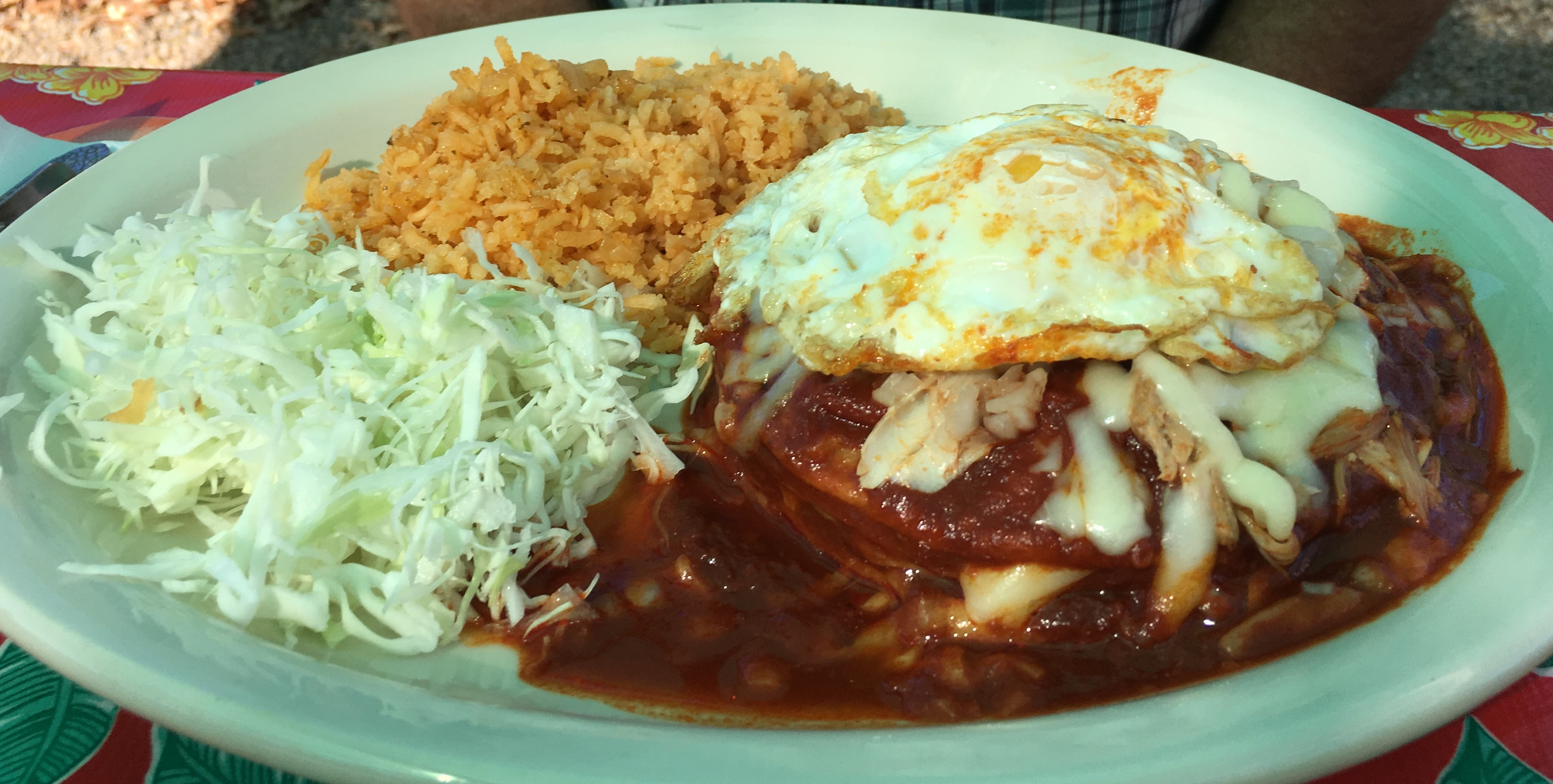 Chicken enchiladas with red sauce and an egg on top, with rice and cabbage.