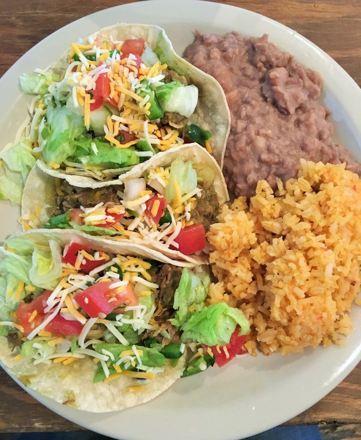 Chile Verde taco plate with beans and rice.