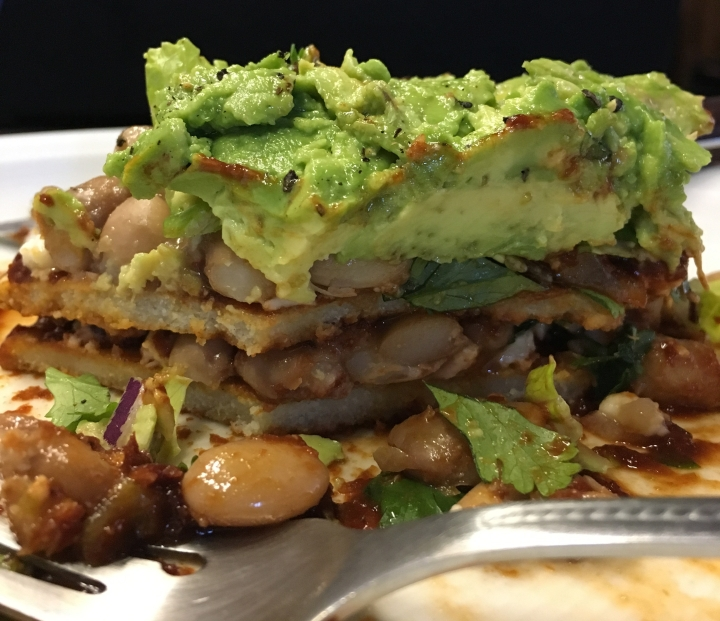 Inside my stack of red with beans and homemade tortillas, topped with guacamole.